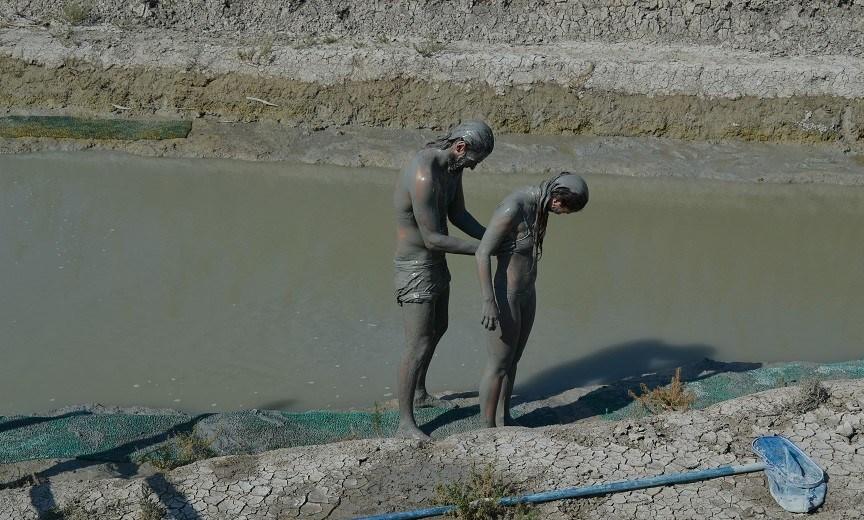 Man smeert jonge vrouw in met modder